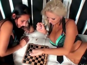 Two busty lesbians are playing chess and petting each other during the game