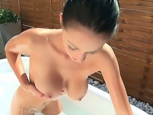 Brunette Nicole Smith enjoys having a refreshing bath while rubbing her soft...