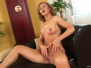 Slim mature woman takes off her white panties to masturbate.