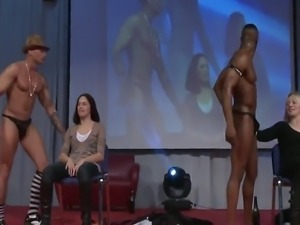 Handsome male stripper seducing and teasing a beautiful girl on the stage