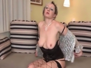 Blonde mature in fishnets rubs her pink cunt