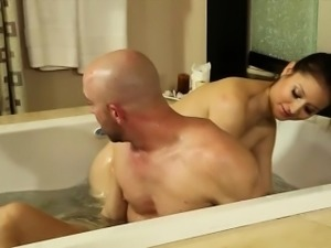 Sexy brunette masseuse giving oral massage in jacuzzi