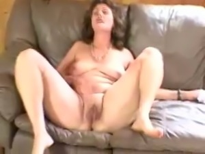 Mature brunette white woman on the couch masturbates with a dildo