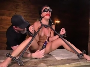 This pretty brunette milf is placed in a special metal bondage device and...