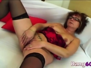 A slutty older woman rubs her pussy before